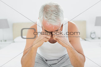 Thoughtful mature man sitting in bed