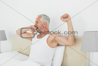 Mature man stretching his arms at home