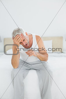Thoughtful mature man yawning sitting in bed
