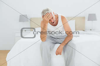 Thoughtful mature man yawning in bed
