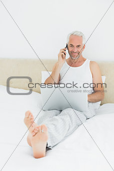 Casual smiling mature man using cellphone and laptop in bed