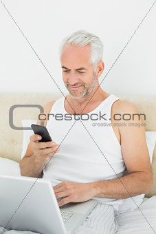 Mature man with cellphone and laptop in bed