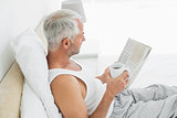 Mature man with coffee cup and newspaper in bed