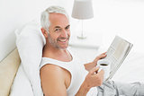 Smiling mature man with coffee cup and newspaper in bed