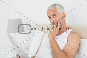 Casual thoughtful mature man with newspaper in bed