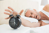 Sleepy mature man extending hand to alarm clock