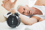 Mature man extending hand to alarm clock in bed