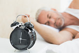 Man sleeping in bed with alarm clock in foreground