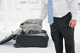 Mid section of a businessman unpacking luggage
