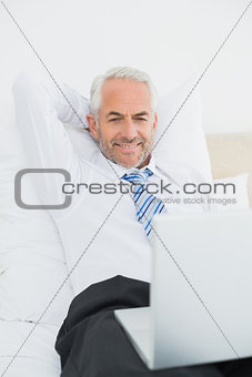 Mature businessman looking at laptop in bed