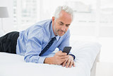 Smiling relaxed businessman text messaging in bed