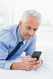 Relaxed businessman text messaging in bed