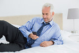 Relaxed well dressed man text messaging in bed