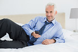 Smiling well dressed man text messaging in bed