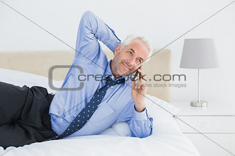 Mature businessman using mobile phone in bed