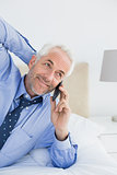 Relaxed mature businessman using mobile phone in bed
