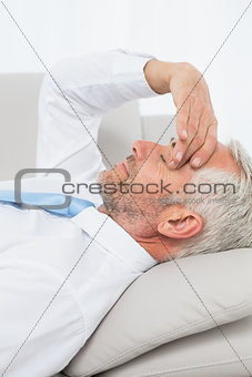 Tired mature businessman resting on sofa