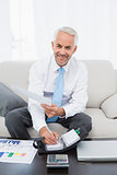 Smiling businessman with graphs and diary at home