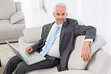 Businessman using laptop on sofa at home