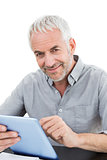 Portrait of a smiling mature businessman using digital tablet