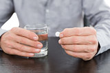 Mid section of a man holding glass of water and pill