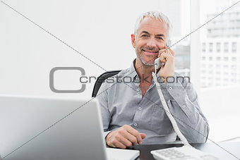 Smiling businessman on call in front of laptop at office desk
