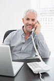 Businessman using telephone in front of laptop at office desk