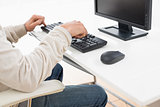 Side view mid section of a man using computer keyboard