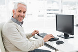 Smiling mature man using computer at desk in office