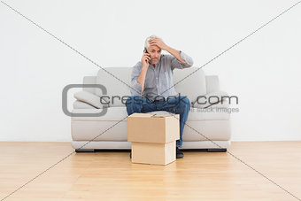 Annoyed man using cellpone on sofa with boxes in house