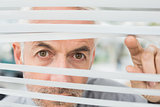 Close-up of a mature businessman peeking through blinds