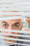 Close-up of a serious businessman peeking through blinds