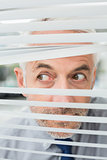 Close-up of a businessman peeking through blinds