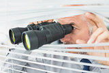 Mature businessman peeking with binoculars through blinds