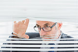 Serious mature businessman peeking through blinds in office