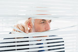 Close-up of a businessman peeking through blinds in office