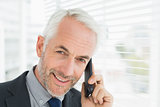 Close-up of smiling mature businessman using cellphone