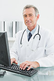 Smiling male doctor using computer at office