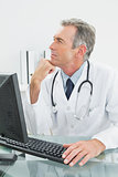 Thoughtful doctor with computer at office