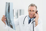 Doctor with x-ray picture using telephone at office