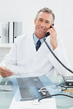 Smiling male doctor using telephone at office