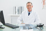 Smiling confident male doctor at desk in office