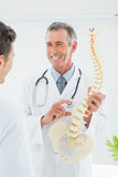 Cheerful doctor explaining spine to patient in office