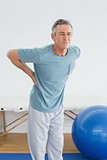 Man with lower back pain in the hospital gym