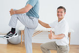 Therapist massaging mans lower back while gesturing thumbs up