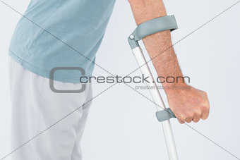 Close-up mid section of a man with crutch