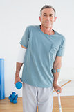 Smiling mature man with crutch and dumbbell