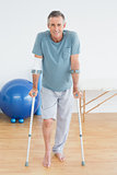 Smiling mature man with crutches at gym hospital