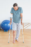 Mature man with crutches at gym hospital