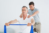 Therapist massaging mans shoulder in gym hospital